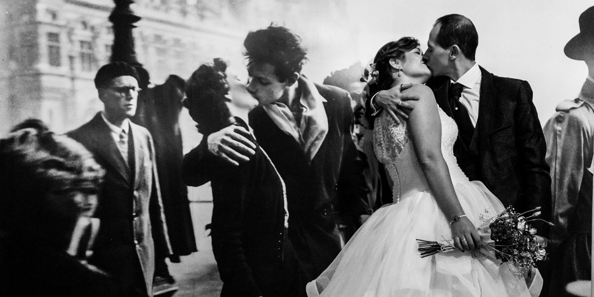 novios besándose frente a cartel de beso