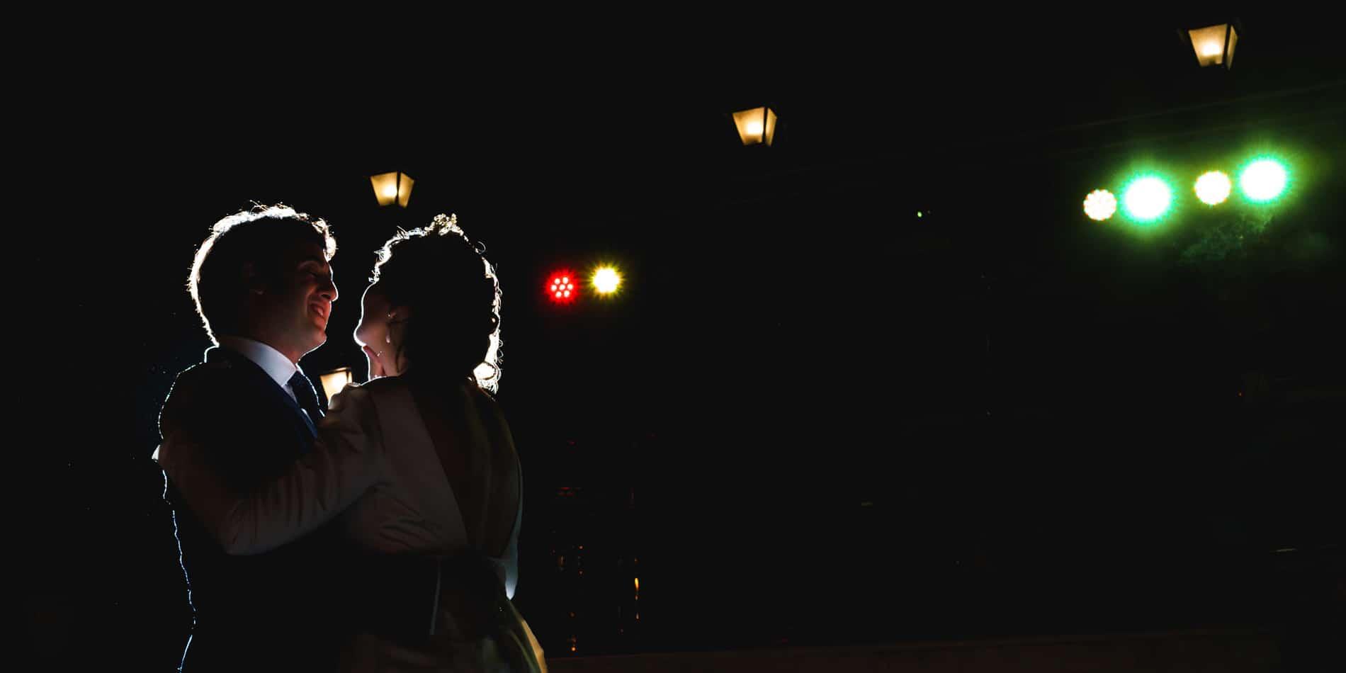 novios en baile nupcial a contraluz con focos de fonde