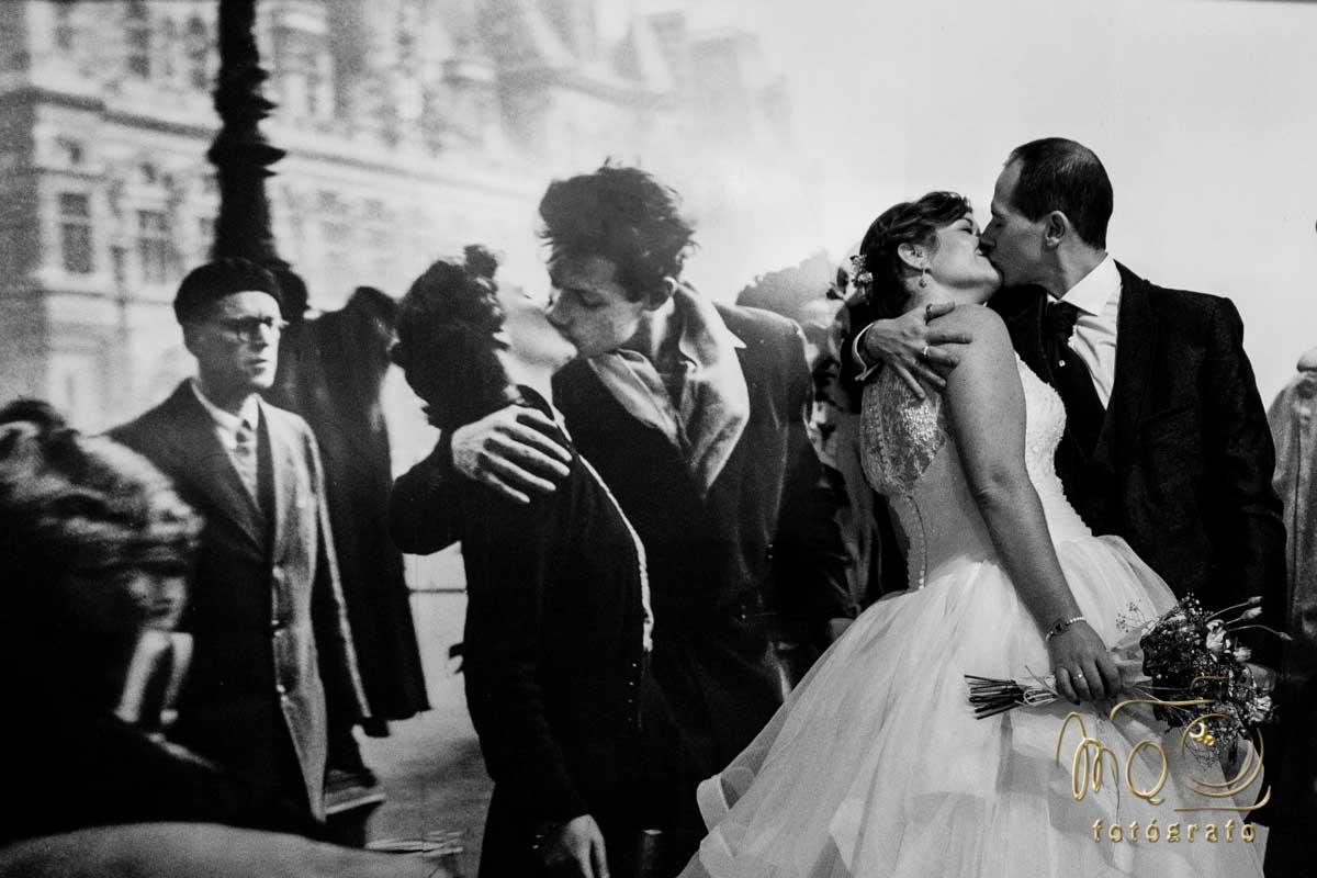 Pareja de novios besándose en su postboda frente a un cartel de pareja con beso