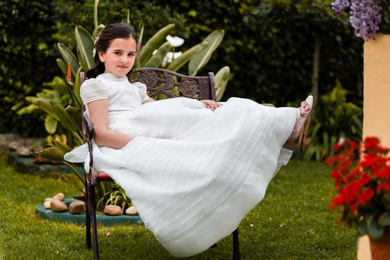 niña vestida de comunión sentada el sillón con los piés en alto