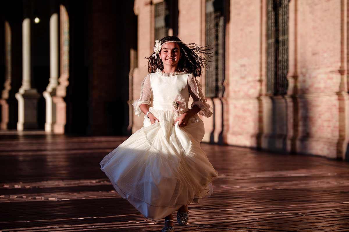 Fotógrafo de comuniones Sevilla, niña de comunión corriendo por plaza de España